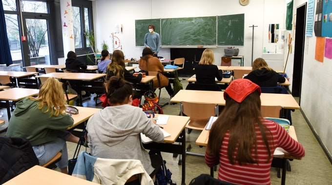 Schüler und Schülerinnen sitzen an ihren Tischen, schreiben und hören dem Lehrer zu.