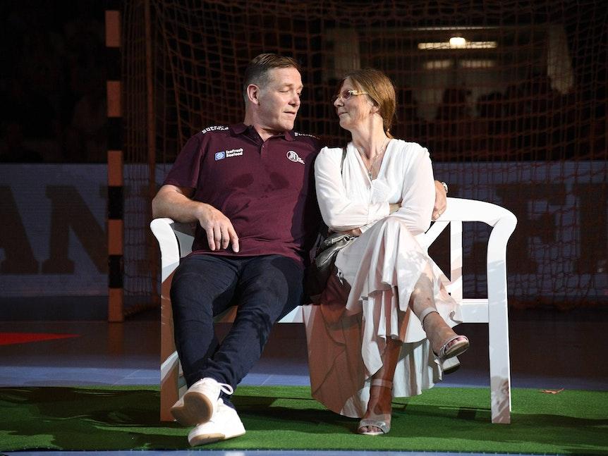 Trainer Alfred Gislason sitzt mit Ehefrau Kara bei seinem Abschiedsspiel für den THW Kiel auf einer Bank.