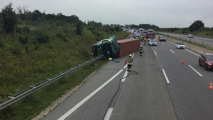 Ein Lkw liegt zur Seite gekippt auf der Leitplanke der Autobahn.