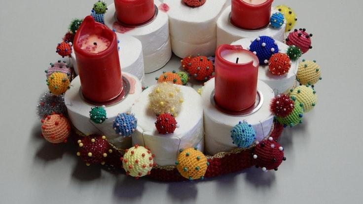 Ein Adventskranz auch acht Klopapierrollen, vier Kerzen und gehäkelten Corona-Viren.