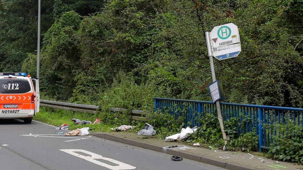 Das Schild einer Bushaltestelle ist umgebogen, ein kleines Rad und andere Gegenstände liegen davor verstreut.