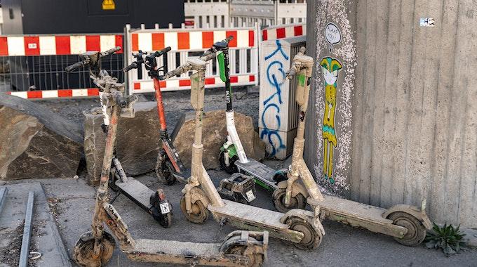 Mit getrocknetem Schlamm und Schmutz bedeckte E-Scooter stehen an einer Mauer.