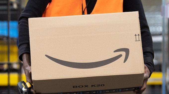 Ein Sortiermitarbeiter von Amazon trägt in einem Verzeilzentrum ein Paket.