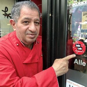 Carmelo Faraci zeigt auf den Jode-Lade-Aufkleber auf der Fensterscheibe des Lokals.
