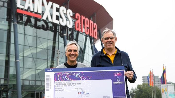 Ein Jahr vor dem Turnierstart: Die Kölner Basketball-Legenden Stefan Baeck und Klaus Zander präsentieren ein symbolisches Ticket für die Basketball-EM 2022 in Köln und Berlin.