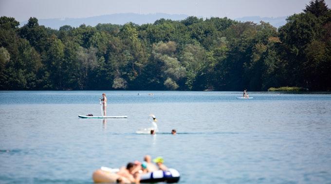 Badegäste genießen das schöne Wetter am Opfinger See in Baden-Württemberg.