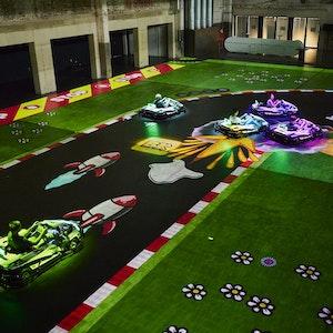 Fünf Elektro-Karts fahren auf einer auf den Boden projizierten Strecke.