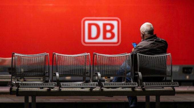 Das Logo der Deutschen Bahn (DB) prangt an der Seite einer Lok, während ein Mann in München am Donnerstag (2. September) auf dem Hauptbahnhof wartet. Die Deutsche Bahn geht gerichtlich gegen den GDL-Streik vor.