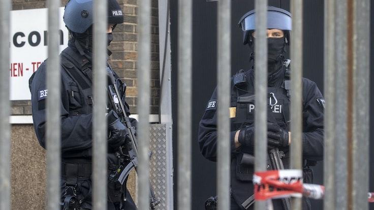 Polizisten stehen vor einem abgesperrten Gebäude.