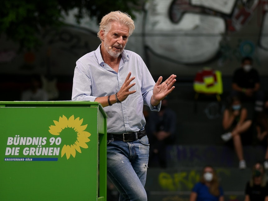 Frank Schätzing redet an einem grünen Pult auf dem Wilhelmsplatz.