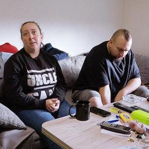 Petra und Sascha sitzen an ihrem Wohnzimmertisch in Mannheim.
