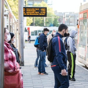 Zahlreiche Pendler warten am Morgen mit verschiedenen Gesichtsbedeckungen vor einer Straßenbahn in Düsseldorf (Archivbild vom April 2020): In Düsseldorf wurde ein Mann mit einem regenbogenfarbenen Mund-Nase-Schutz beleidigt und körperlich angegriffen.