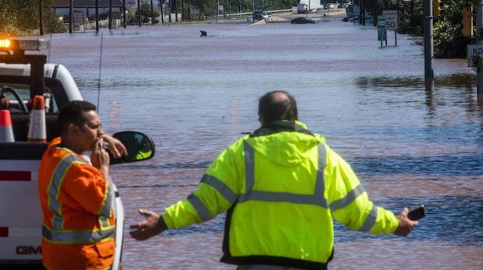Menschen stehen an der überfluteten Bundesstraße 206 in New Jersey. Im Hintergrund sind überflutete Autos zu sehen.