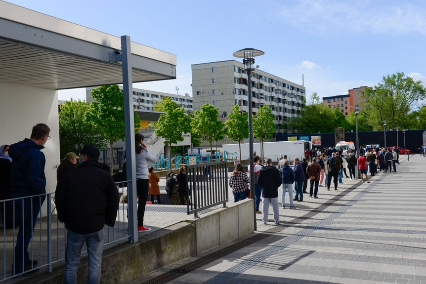 Menschen warten in Köln-Finkenberg in der Schlange auf ihre Impfung.