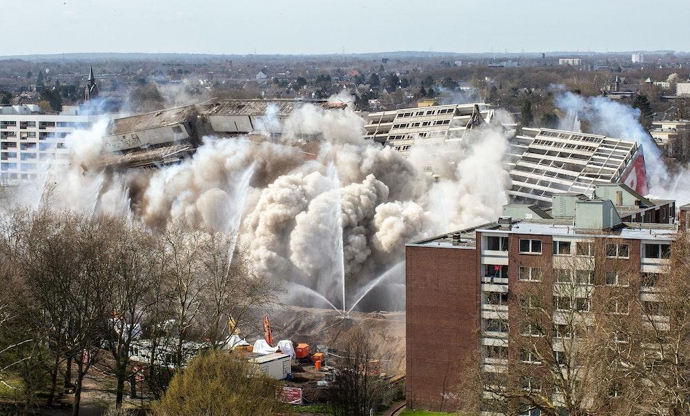 """Das als """"Weißer Riese"""" bekannte Hochhaus fällt in einer riesigen Staubwolkee in sich zusammen. Das Gebäude aus dem Jahr 1972 hatte einst 320 Wohnungen. Es galt als eines der größten Wohnhäuser in Nordrhein-Westfalen."""