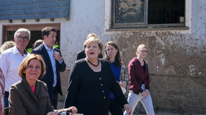 German Chancellor Angela Merkel, center, and Malu Dreyer, left, Prime Minister of Rhineland-Palatinate, talk to residents during their visit to the flood-damaged district Altenburg, part of the municipality of Altenahr, Germany, on September 3, 2021. - After days of extreme downpours, devastating floods hit the valley of the river Ahr in July 2021. (Photo by Markus Schreiber / POOL / AFP)