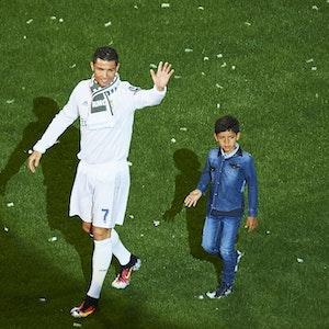 Cristiano Ronaldo und sein Sohn Cristiano Jr. laufen über den Platz von Real Madrid.