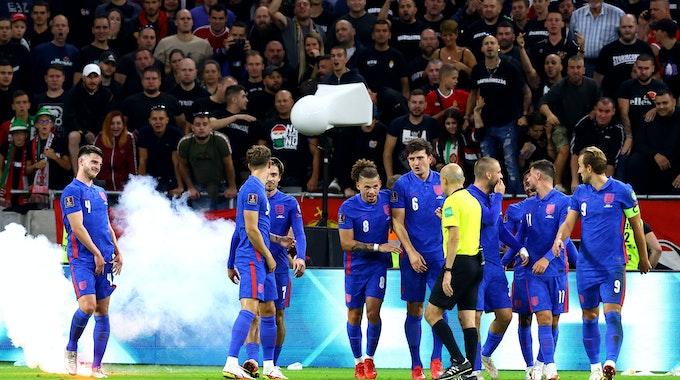Englische Spieler stehen vor ungarischem Publikum, das sie beschimpft.