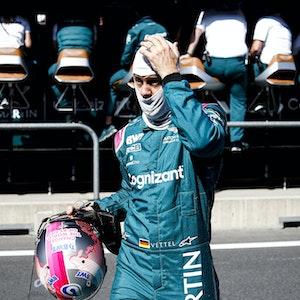Sebastian Vettel mit Helm in der Hand und Gesichtsmaske auf dem Kopf fasst sich an den Kopf.