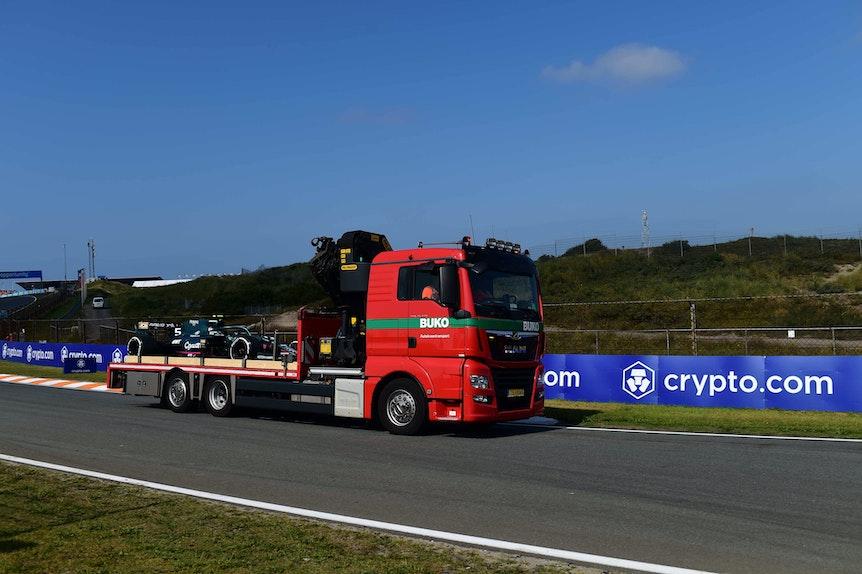 Ein roter Transporter schleppt Vettels Auto ab.