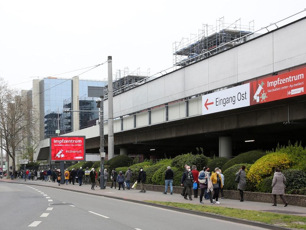 Menschen warten vor dem Impfzentrum Köln auf ihre Impfung.