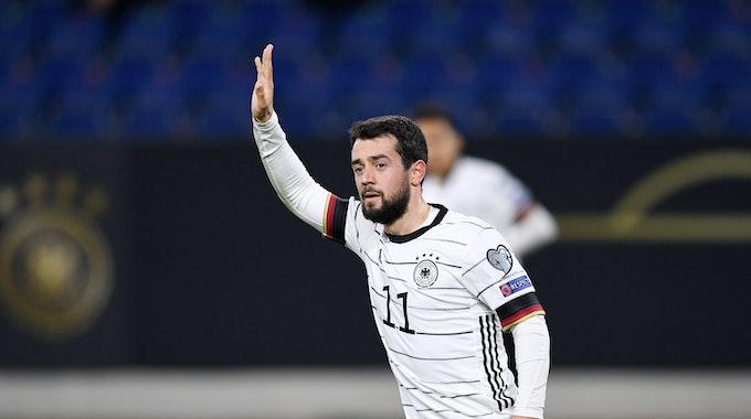 Amin Younes im Trikot der deutschen Nationalmannschaft hebt den Arm.
