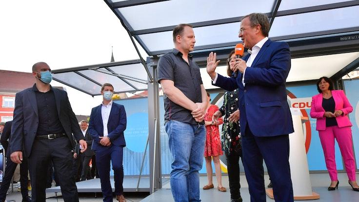 Armin Laschet spricht während einer Veranstaltung in Erfurt am 3. September mit einem Mann, der auf das Podium gesprungen ist.