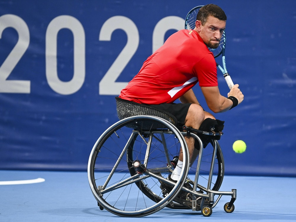 Joachim Gerard sitzt in seinem Rollstuhl und holt zu einem Rückhandschlag aus.