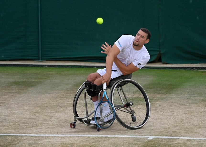 Joachim Gerard sitzt auf seinem Rollstuhl und hat gerade einen Aufschlag ausgeführt.