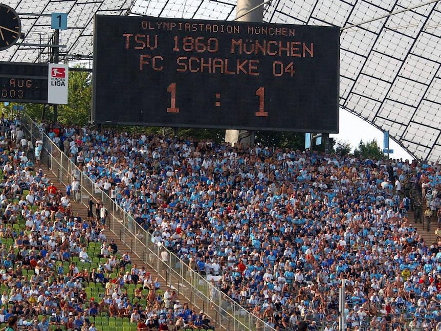 Das Bild zeigt die Anzeigetafel im Olympiastadion. Zwischen 1860 und Schalke steht es 1:1.
