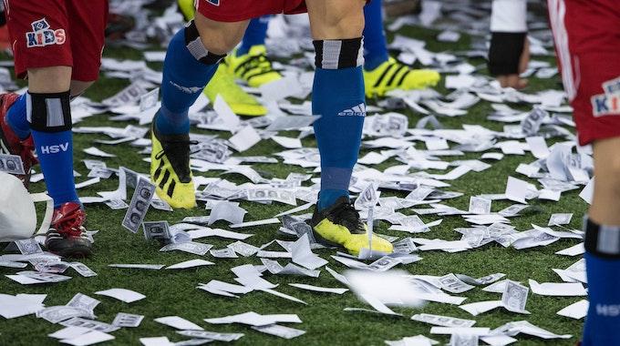Auf dem Boden des Volksparkstadions in Hamburg liegen viele Spielgeldscheine.