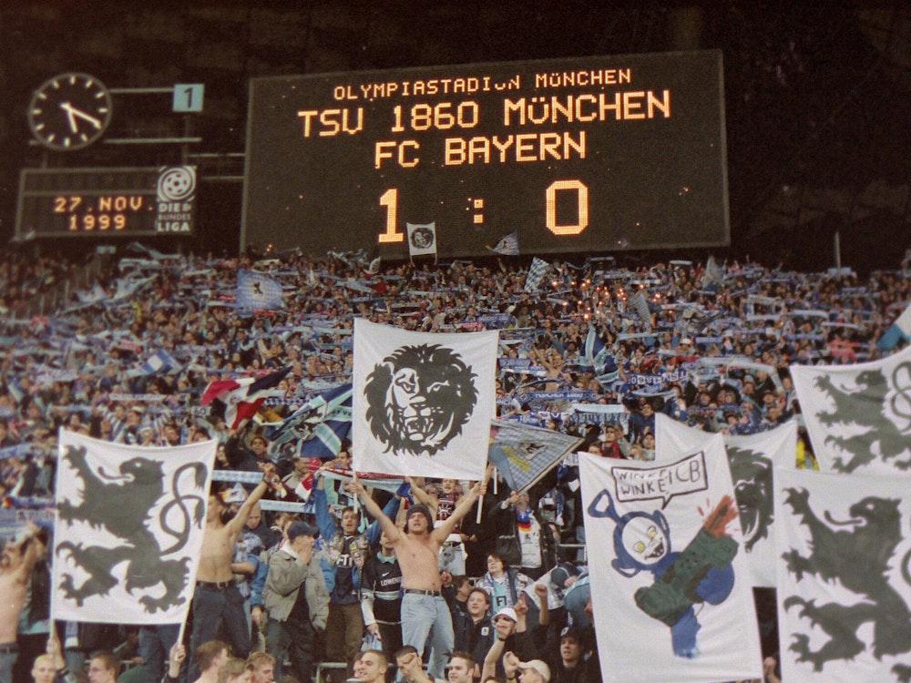 Auf der Anzeigetafel steht, dass 1860 mit 1:0 gegen Bayern gewonnen hat. Darunter freuen sich die Fans der Löwen.