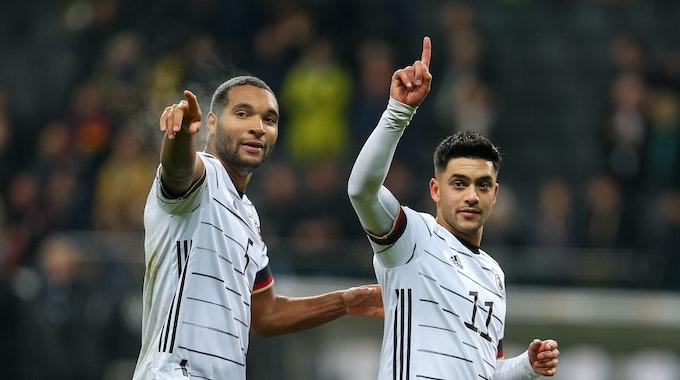 Nadiem Amiri und Jonathan Tah heben ihre Zeigefinger.