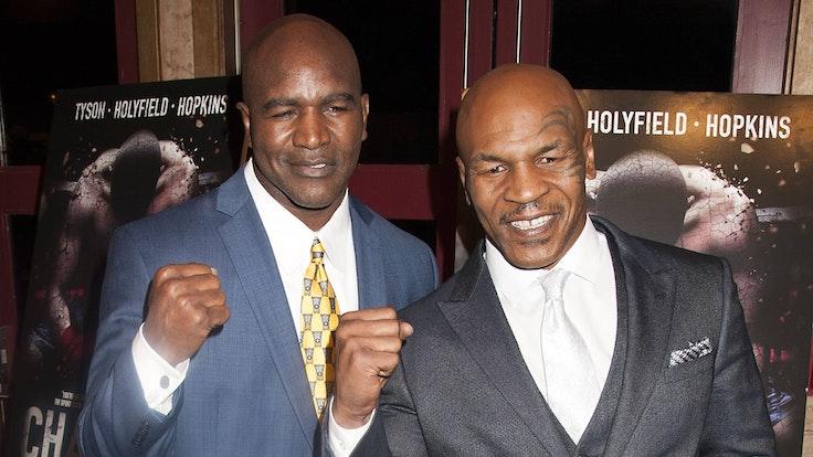 Evander Holyfield und Mike Tyson ballen die Fäuste.