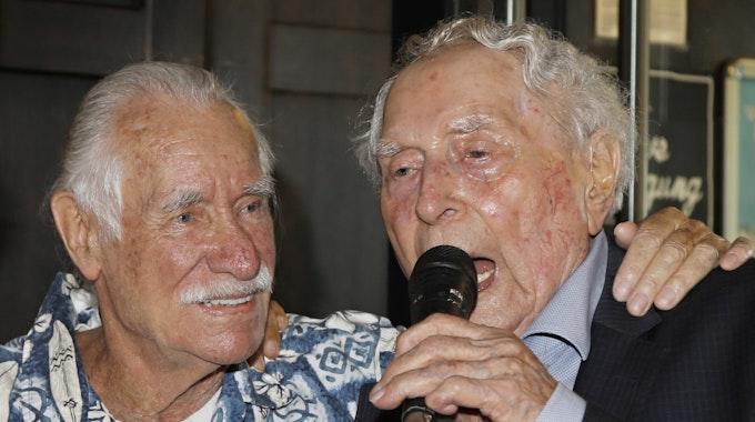 Ludwig Sebus spricht ins Mikrophon, neben ihm Hans Süper.