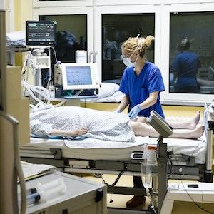 Krankenschwester am Bett eines Intensivpatienten.