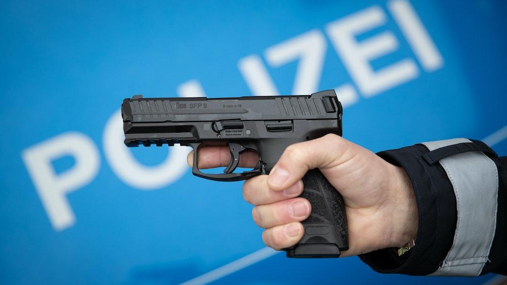 Ein Polizist hält eine Dienstwaffe der Polizei Niedersachsen in einer gestellten Situation in der Hand.