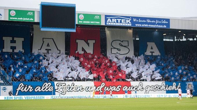 """Die Kurve des Hansa-Fans im Ostseestadion ist bedeckt mit blauen, roten und weißen Fahnen und einem Schriftzug: """"Hansa – für alle Zeiten und was auch geschieht""""."""