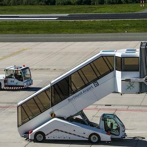 """Eine Gangway mit der Aufschrift """"Dortmund Airport"""" steht auf dem Flughafen."""