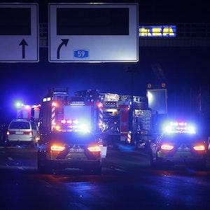Fahrzeuge der Feuerwehr stehen mit Blaulicht auf der Autobahn.