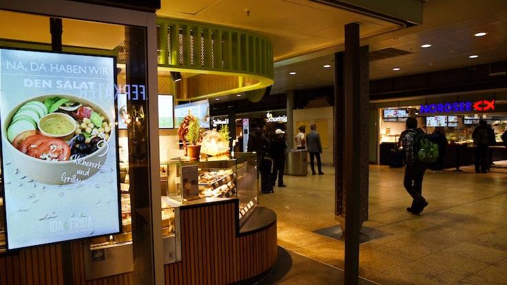Die Ladenzeile im Kölner Hauptbahnhof bei Dunkelheit.