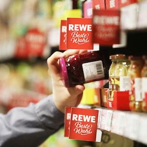 Ein Mann nimmt in unserem Symbolbild ein Glas aus dem Regal einer Rewe-Filiale. Vielerorts sind wieder Weihnachtsprodukte erhältlich, die Kundschaft zeigt sich auf Twitter gespalten.