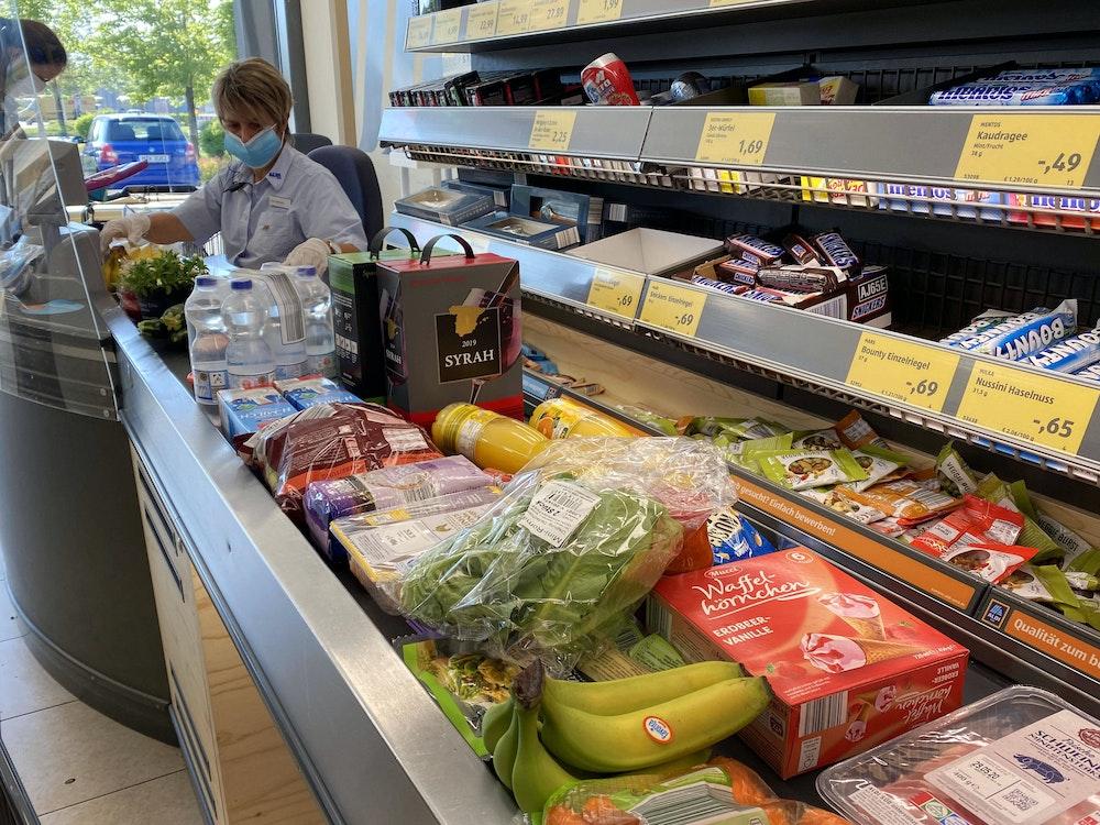 Lebensmittel liegen auf einem Kassenband an einer Supermarktkasse.