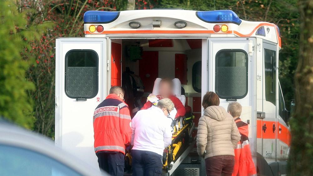 Rettungskräfte schieben am 1. Dezember 2015 in Lindern im Landkreis Cloppenburg (Niedersachsen) einen auf einer Trage liegenden Verletzten in einen Krankenwagen.