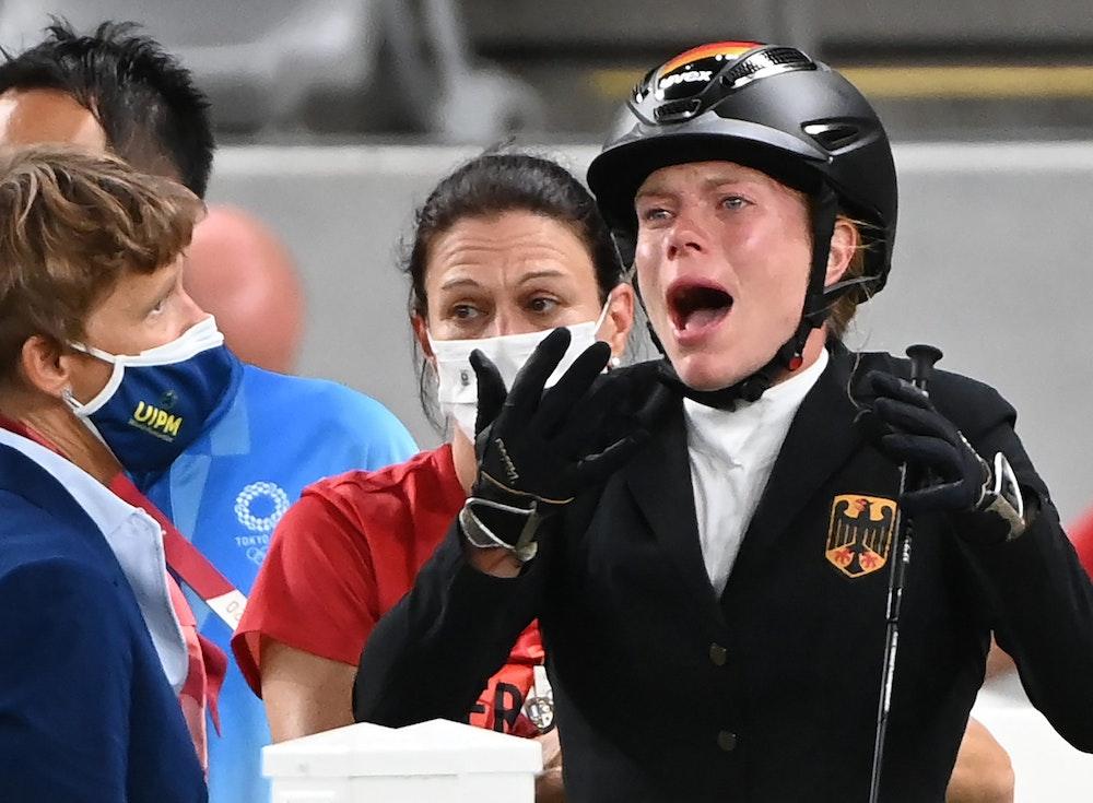 Springreiten im Tokio Stadium: Annika Schleu (r) aus Deutschland weinter, weil ihr Pferd nicht springen wollte, hinter ihr stand Bundestrainerin Kim Raisner.