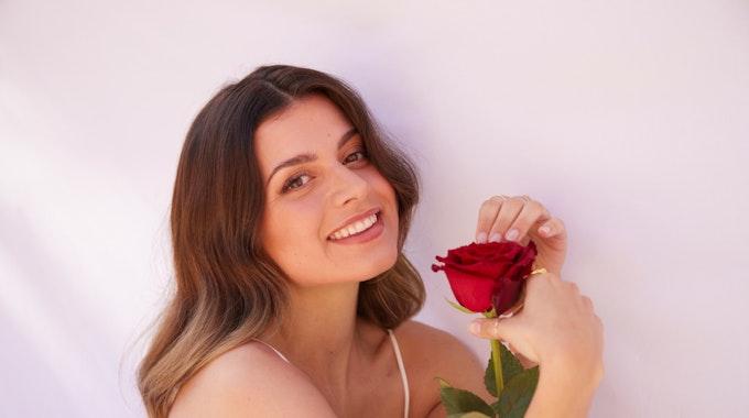 """""""Bachelorette"""" Maxime lächelt in die Kamera und hält eine Rose in der Hand."""