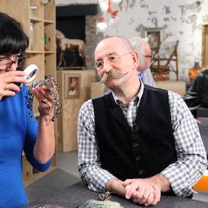 """Heide Rezepa-Zabel, Kunsthistorikerin und Kunstsachverständige, und Horst Lichter, Moderator der ZDF-Sendung """"Bares für Rares"""", betrachten am Experten-Tisch ein Schmuckstück."""