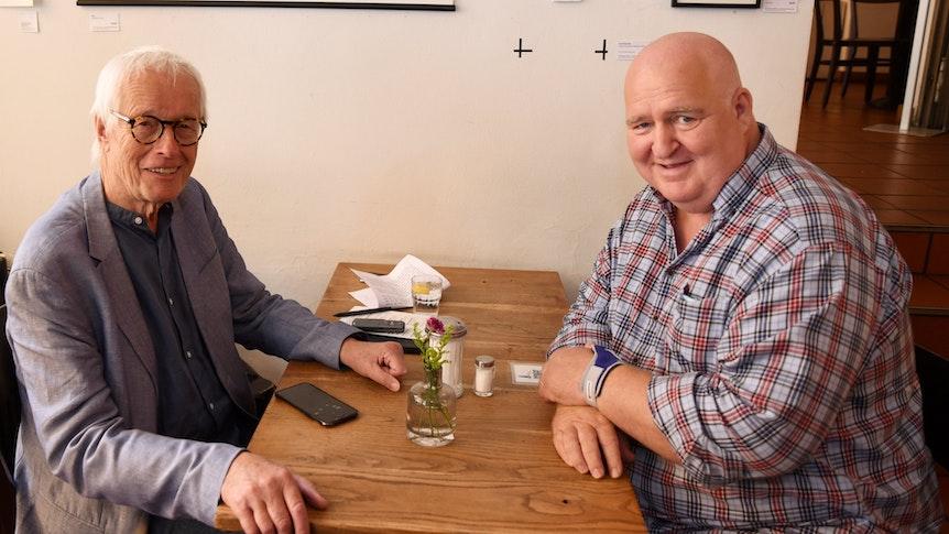 Express-Reporter Horst Stellmacher und Markus Maria Profitlich sitzen an einem Tisch.