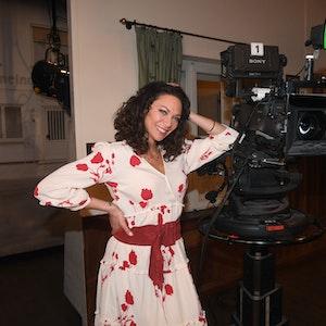 """Das Model Lilly Becker steht in der Kulisse des """"Brunnerwirt"""" der Familienserie des Bayerischen Rundfunks """"Dahoam is Dahoam"""" neben einer Kamera."""