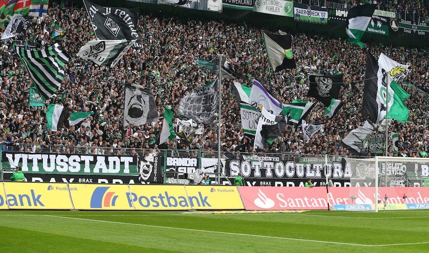 Gladbach-Fans in der Nordkurve im Borussia-Park. Auf diesem Foto am 5. Oktober 2013 zu sehen. Die Fans schwenken Fahnen.